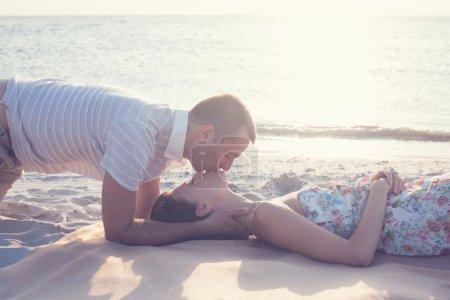 Photo pour Beau couple couché et embrassant sur la plage. mec baisers sur le dessus - image libre de droit