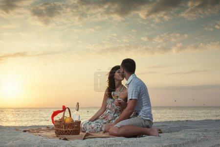 Photo pour Couple Sur La Plage Avec Pique-nique De Vin De Luxe Au Coucher Du Soleil. Aube - image libre de droit