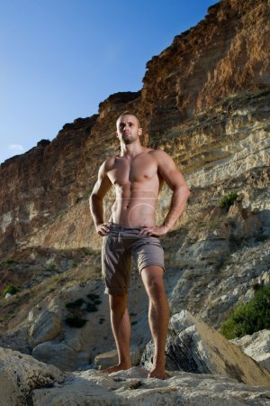 Perfect body man with naked torso on mountains.brown trousers