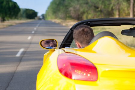 Back view of a young man driving his convertible yellow car. Open roof