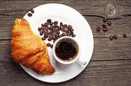 Photo for Coffee cup with a croissant on vintage wooden table. Top view - Royalty Free Image