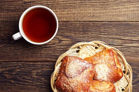 Photo for Sweet buns and cup of hot tea on wooden table. Top view - Royalty Free Image