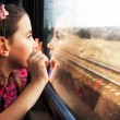 Little girl looking through window. She travels on...