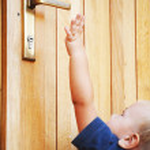 Little boy try to reach door-handle...