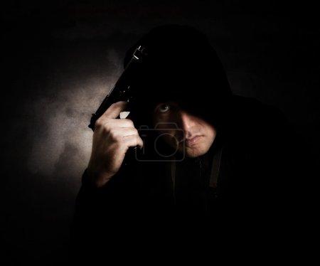 Photo pour Membre d'un gang portait un chandail à capuchon noir tenant une arme de poing avec un expression.texture en colère a été ajouté et des céréales est également visible - image libre de droit