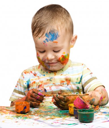 Photo for Portrait of a cute little boy messily playing with paints, isolated over white - Royalty Free Image