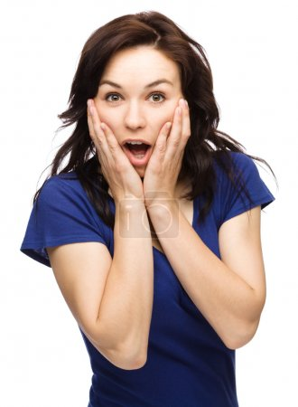 Woman is holding her face in astonishment
