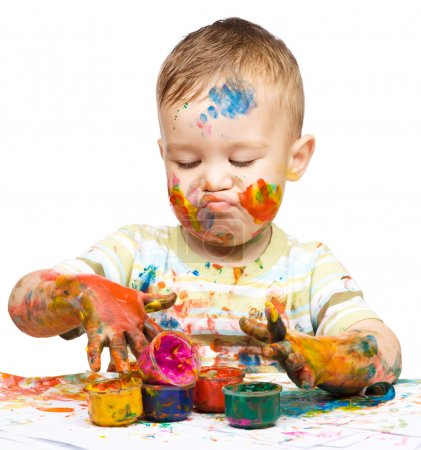 Photo for Portrait of a cute little boy messily playing with paints while making funny grimace, isolated over white - Royalty Free Image