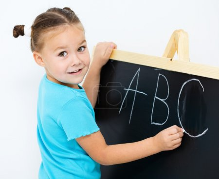 Photo pour Petite fille mignonne montre la lettre E sur l'alphabet à l'école maternelle - image libre de droit