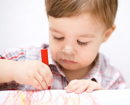 Photo for Little boy is drawing on white paper using crayon - Royalty Free Image