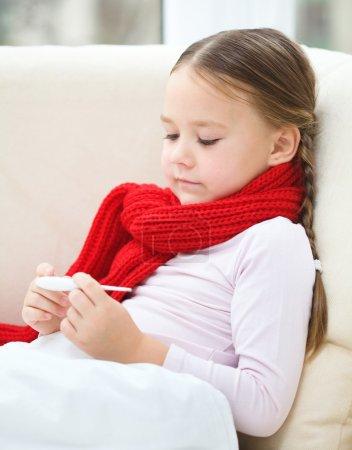 Photo pour Petite fille malade lit thermomètre tout en étant couché sur le canapé - image libre de droit