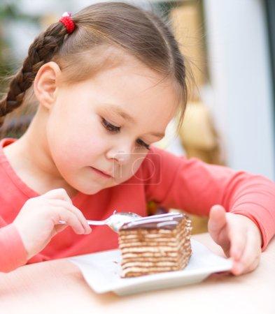 Photo pour Petite fille mignonne mange gâteau dans le salon - image libre de droit
