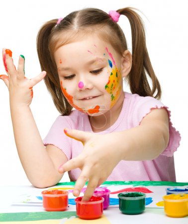 Photo for Portrait of a cute cheerful girl playing with paints, isolated over white - Royalty Free Image
