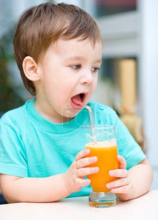 Photo for Little boy is drinking orange juice using straw - Royalty Free Image