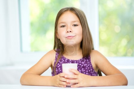 Photo for Cute little girl is showing milk moustache - Royalty Free Image