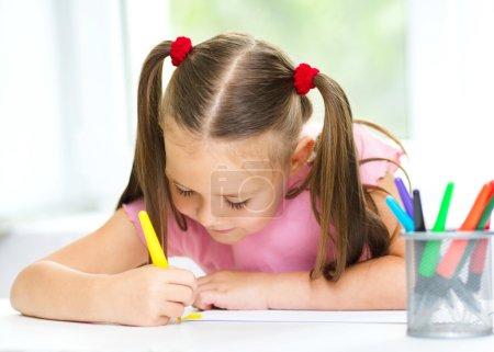 Photo pour Mignon dessin joyeux enfant à l'aide d'un stylo feutre tout en étant assis à la table - image libre de droit