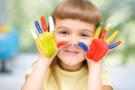 Photo for Portrait of a cute cheerful girl showing her hands painted in bright colors - Royalty Free Image