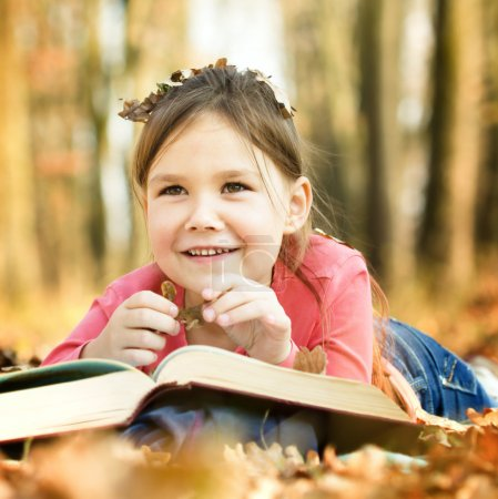 Photo pour Petite fille mignonne lit un livre en plein air - image libre de droit
