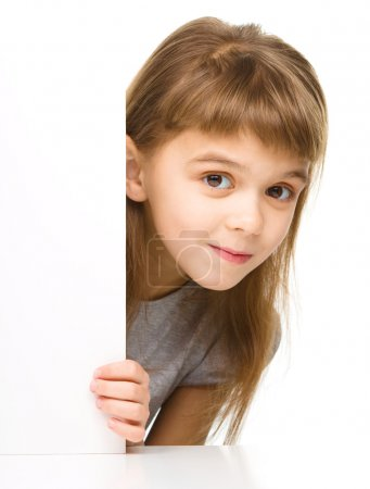 Little girl is looking out from the blank banner