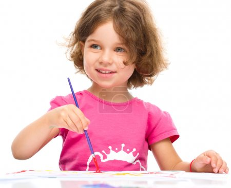 Photo pour Petite fille peint à la gouache alors qu'elle est assise à table, isolée sur du blanc - image libre de droit