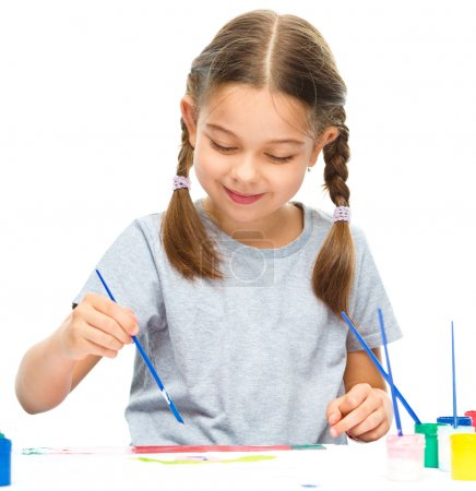 Photo for Little girl is painting with gouache while sitting at table, isolated over white - Royalty Free Image