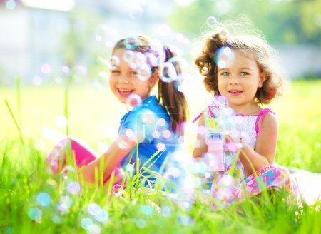 Photo pour Deux petites filles soufflent des bulles de savon, tournent en plein air - image libre de droit