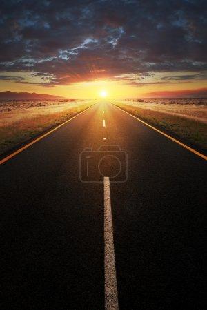 Straight asphalt road leading into sunlight