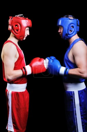 Photo pour Deux boxeurs masculins se battant sur fond noir - image libre de droit