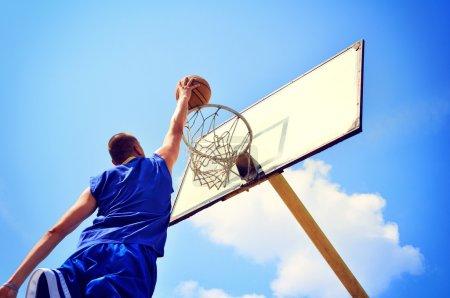 Photo pour Basketball joueur en action volant haut et marquant - image libre de droit
