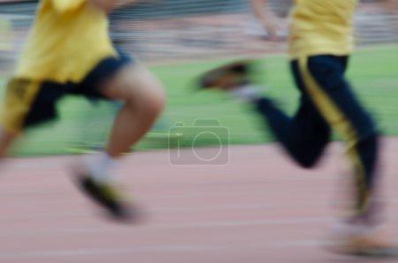 running child on sport track blurred motion