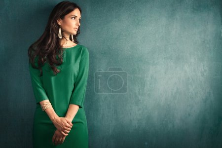 Photo for Elegant mature woman in green dress lean on wall - Royalty Free Image