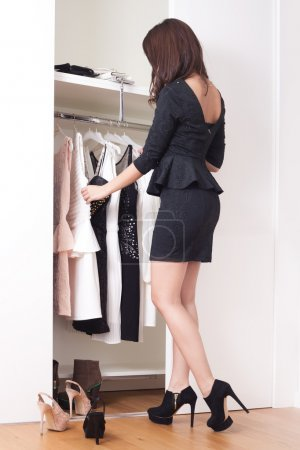 Photo for Young elegant woman in front of open closet full of elegant dresses choose what to wear full body shot - Royalty Free Image