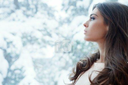 Photo pour Portrait d'hiver de jeune femme par fenêtre - image libre de droit