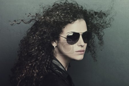 Photo for Curly hair young woman with sunglasses studio shot - Royalty Free Image