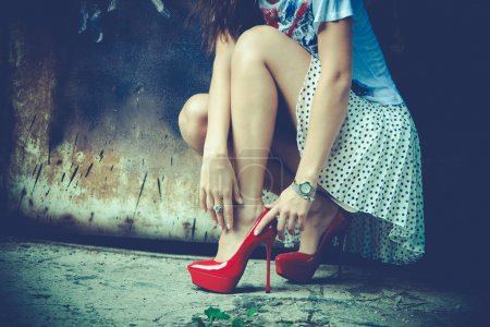Photo for Woman legs in red high heel shoes and short skirt outdoor shot against old metal door - Royalty Free Image