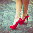 Woman legs in red high heel shoes outdoor shot on ...