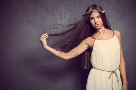 Foto de Natural mujer joven con el pelo largo y recto en blanco simplemente vestido y corona de hojas en pelo studio disparó - Imagen libre de derechos
