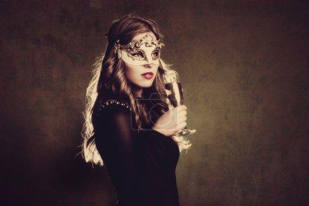 Photo pour Femme blonde avec masque vénitien et verre de champagne studio tourné - image libre de droit