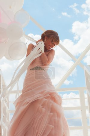 Photo for Young beautiful bride in elegant wedding dress hold balloons  standing on white stairs against sky with clouds - Royalty Free Image