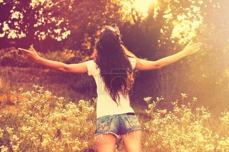 Photo pour Jeune femme en short jeans et t-shirt de dos profiter en journée d'été avec les bras ouverts, rétro couleurs, sun flare - image libre de droit