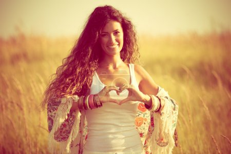 Photo for Smiling young woman in summer field show heart shape hands sign - Royalty Free Image