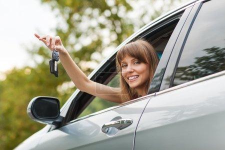 Photo pour Blanc voiture pilote femme souriant montrant de nouvelles clés de voiture et de voiture - image libre de droit