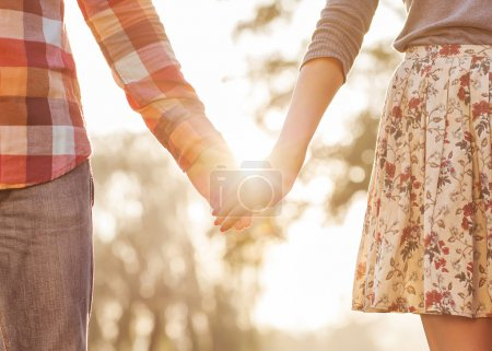 Photo for Young couple in love walking in the autumn park holding hands looking in the sunset - Royalty Free Image