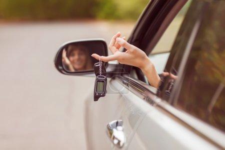 Photo pour Fille joyeuse tenant les clés de voiture de la fenêtre - image libre de droit