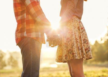 Photo pour Jeune couple amoureux à pied dans le parc automne main dans la main à la recherche au coucher du soleil - image libre de droit