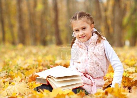 Photo pour Fille dans parc d'automne lecture d'un livre - image libre de droit