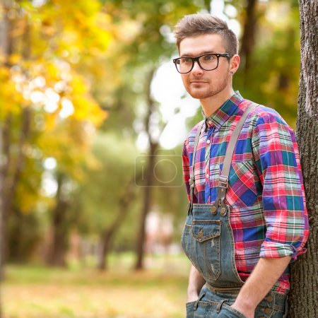 hipster standing in autumn park grin