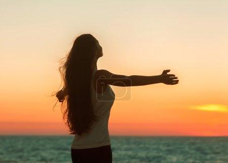 Photo pour Femme libre jouissant de la liberté se sentant heureux à la plage au coucher du soleil. Belle femme relaxante sereine dans le pur bonheur et le plaisir réjoui avec les bras levés tendus vers le haut. Asiatique modèle féminin caucasien . - image libre de droit