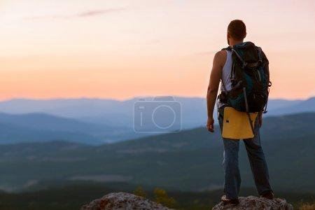 Photo pour Un type dans les montagnes au coucher du soleil. le concept de liberté - image libre de droit