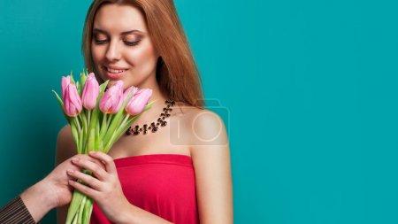 Photo pour Jeune fille belle donne un bouquet d'homme de tulipes, tenant la main avec un bouquet. célébrer la Saint-Valentin - image libre de droit